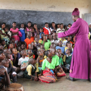 Bishop Godfrey Makumbi in front of a flock of children in Kanoni, Uganda<div class='url' style='display:none;'>/en/</div><div class='dom' style='display:none;'>kirchgemeinde.ch/en/</div><div class='aid' style='display:none;'>410</div><div class='bid' style='display:none;'>11601</div><div class='usr' style='display:none;'>235</div>