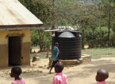 Making improvements with little investment —  During the rainy season runoff from the Kanoni schoolhouse roofs is collected into storage tanks for later use.